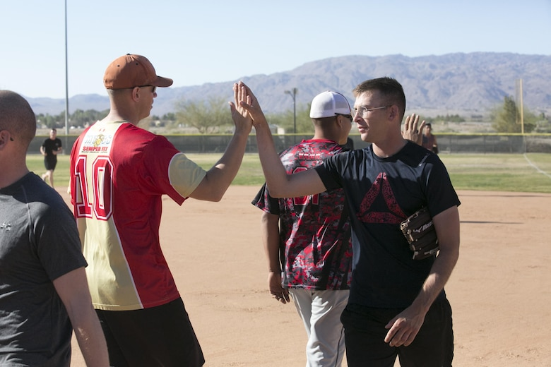 Sgt. John Evans, assault amphibious vehicle crewman, 3rd Amphibian Assault Battalion, and Sgt. Blake Seekamp, military working dog handler, Provost Marshalls Office, Headquarters Battalion, display good sportsmanship after a game by exchanging high-fives during the Marine Corps Tactics and Operations Group annual Softball Tournament held at Felix Field, March 26, 2016. (Official Marine Corps photo by Cpl. Medina Ayala-Lo/ Released)