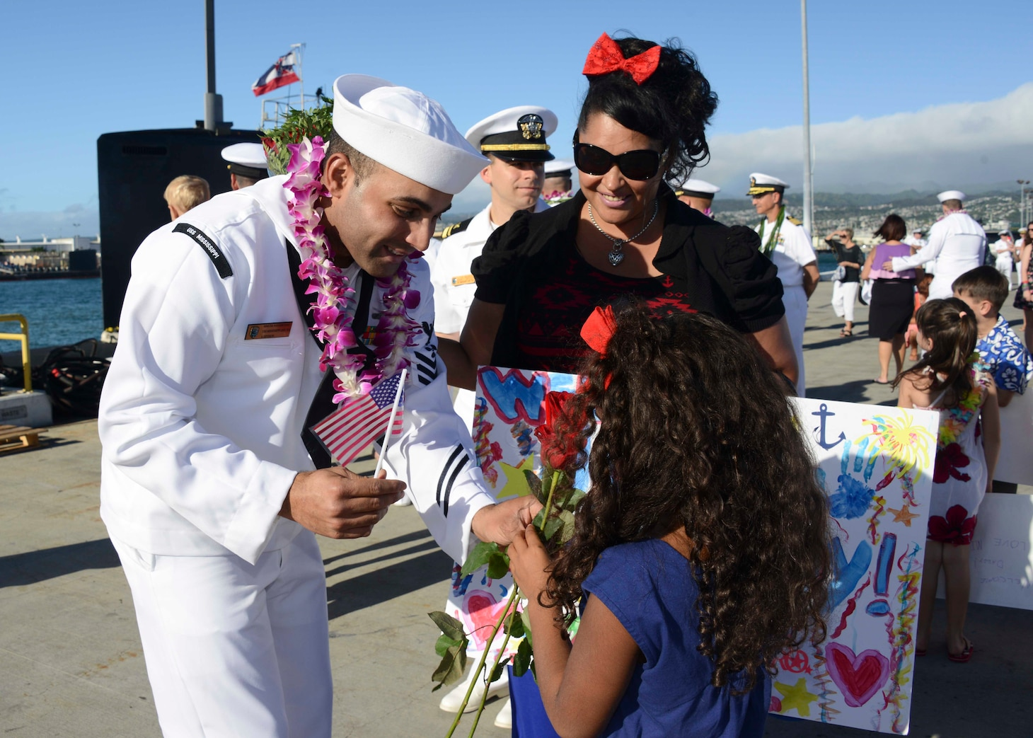141125-N-DB801-293 PEARL HARBOR (Nov. 25, 2014) Machinist's Mate 1st Class Luis Navarrodiaz, assigned to the Virginia-class attack submarine USS Mississippi (SSN 782), greets his daughter wife and daughter as the submarine arrives at Joint Base Pearl Harbor-Hickam for a change of homeport from Commander, Submarine Squadron (SUBRON) 4 in Groton, Conn., to SUBRON-1. Mississippi is the 4th Virginia-class submarine to be home ported in Pearl Harbor, and one of 18 attack submarines permanently homeported at the historic base. (U.S. Navy photo by Mass Communication Specialist 1st Class Steven Khor/Released)