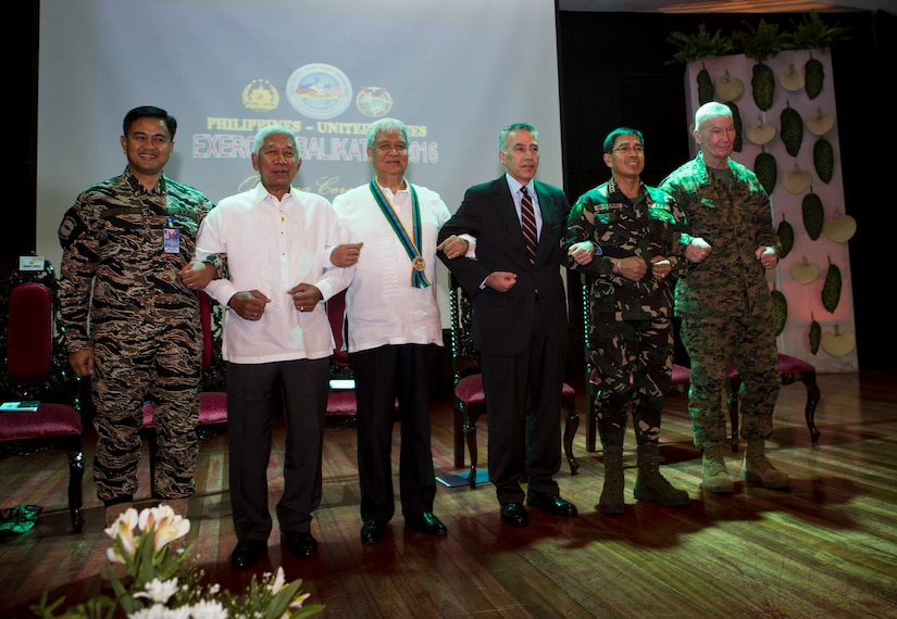 """The official party including government officials and military leaders from the Armed Forces of the Philippines and United States, stand together for a photo at the opening ceremony of Balikatan 2016, aboard Camp Aguinaldo, April 4, 2016. Balikatan, which means """"shoulder to shoulder"""" in Filipino, is an annual bilateral training exercise focused on improving the ability of Philippine and U.S. military forces to work together during planning, contingency and humanitarian assistance and disaster relief operations. This year marks the 32nd iteration of the exercise. (U.S. Marine Corps photo by Sgt. Erik Estrada)"""