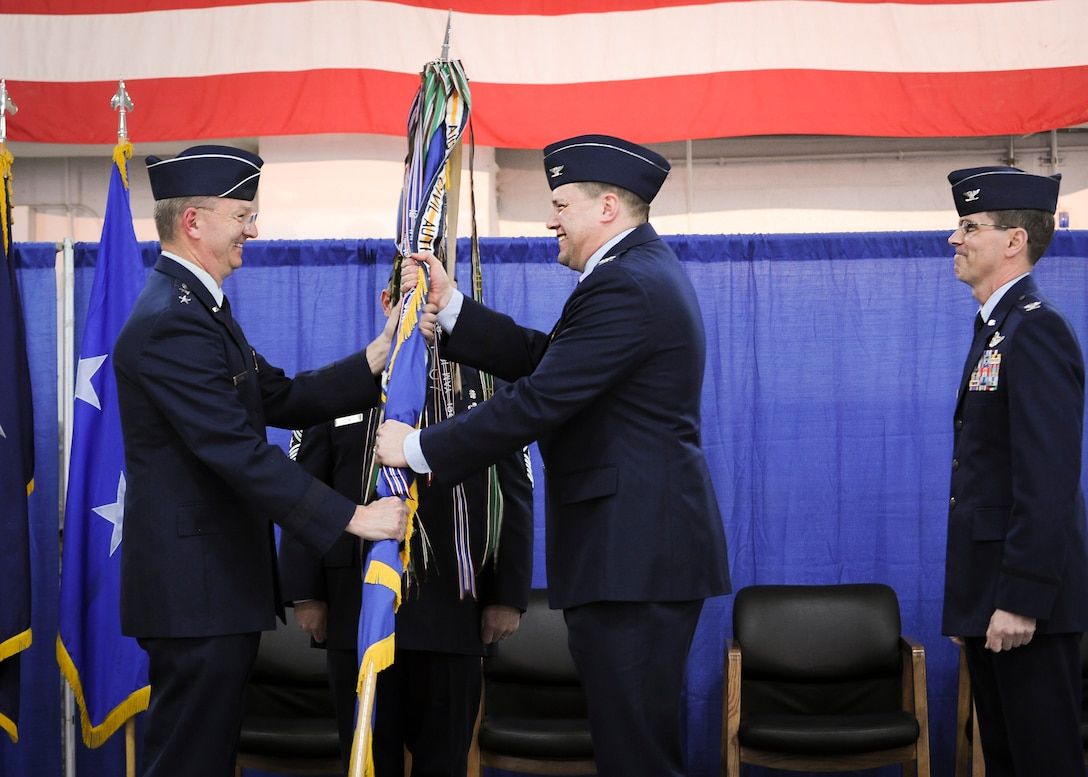 Col. Michael Smith, 174th Attack Wing commander, receives the wing's colors from Maj. Gen. Anthony German, the commander of the New York Air National Guard, during the change of command ceremony held at Hancock Field Air National Guard Base, April 3. (U.S. Air National Guard photo by Tech. Sgt. Jeremy Call/Released)