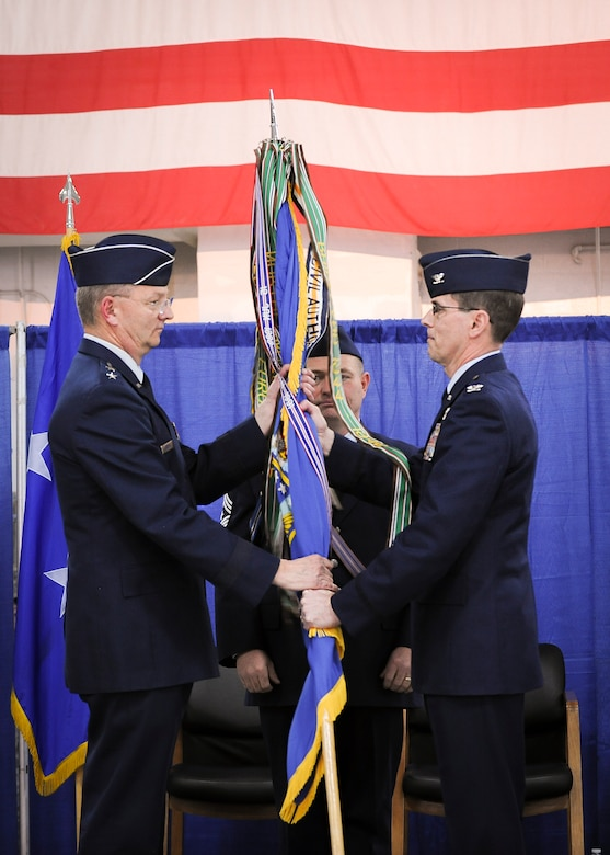 Col. Greg Semmel, 174th Attack Wing commander, hands the wing's colors over to Maj. Gen. Anthony German, the commander of the New York Air National Guard, signifying the transfer of the command, during a ceremony held at Hancock Field Air National Guard Base, April 3. (U.S. Air National Guard photo by Tech. Sgt. Jeremy Call/Released)