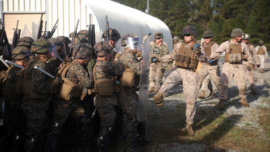 A riot control squad, comprised of Marines with Combat Logistics Battalion 2, battles a notional opposing force during the unit's non-lethal weapons training final exercise at Camp Lejeune, N.C., March 25, 2016. The battalion had to qualify through the Expeditionary Operations Training Group, in preparation for their upcoming deployment with Special Purpose Marine Air-Ground Task Force-Crisis Response-Africa. (U.S. Marine Corps photo by Cpl. Joey Mendez)