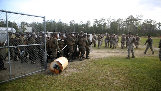 A riot control squad, comprised of Marines with Combat Logistics Battalion 2, faces a notional opposing force during the unit's non-lethal weapons training final exercise at Camp Lejeune, N.C., March 25, 2016. The battalion had to qualify through the Expeditionary Operations Training Group in preparation for their upcoming deployment with Special Purpose Marine Air-Ground Task Force-Crisis Response-Africa. (U.S. Marine Corps photo by Cpl. Joey Mendez)