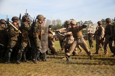 A riot control squad, comprised of Marines with Combat Logistics Battalion 2, confronts a notional opposing force during the unit's non-lethal weapons training final exercise at Camp Lejeune, N.C., March 25, 2016. The battalion had to qualify through the Expeditionary Operations Training Group in preparation for their upcoming deployment with Special Purpose Marine Air-Ground Task Force-Crisis Response-Africa. (U.S. Marine Corps photo by Cpl. Joey Mendez)