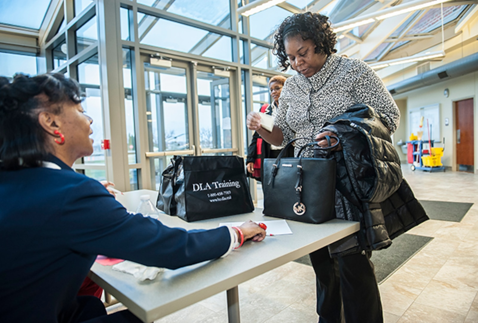One of more than 120 attendees to the Defense Federal Communities Women's Leadership Summit registers prior to the opening kickoff March 23 in the Armed Forces Reserve Center (Building 2). The summit offered two workshops and a panel of four extraordinary women with diverse backgrounds in military, government and public service, sharing their career experiences to enable participants to enhance their leadership skills.