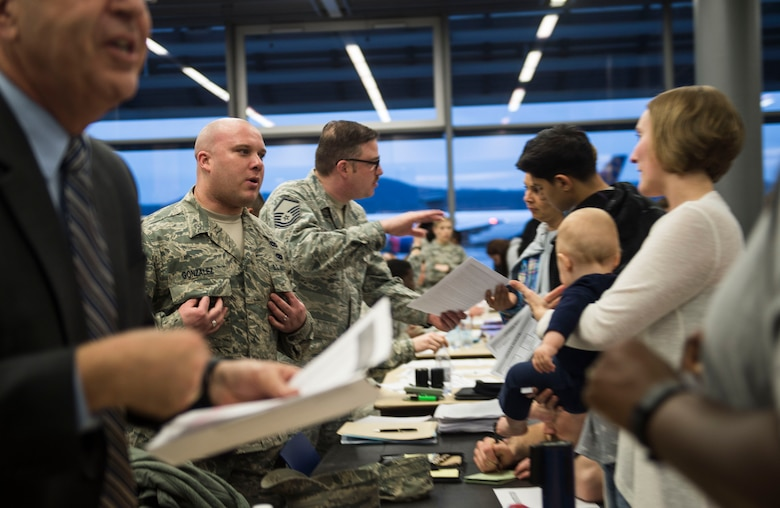 """Airmen from the 86th Airlift Wing process families into Ramstein Air Base, Germany, after their departure from Turkey on March 30, 2016. Because of the ongoing threat in the region, dependents of service members were ordered to leave Turkey and Ramstein AB was designated as a """"transition location"""" for families to await travel to their subsequent duty locations. However, a number of families will relocate to Ramstein AB for an extended period of time. (U.S. Air Force photo/Staff Sgt. Sara Keller)"""