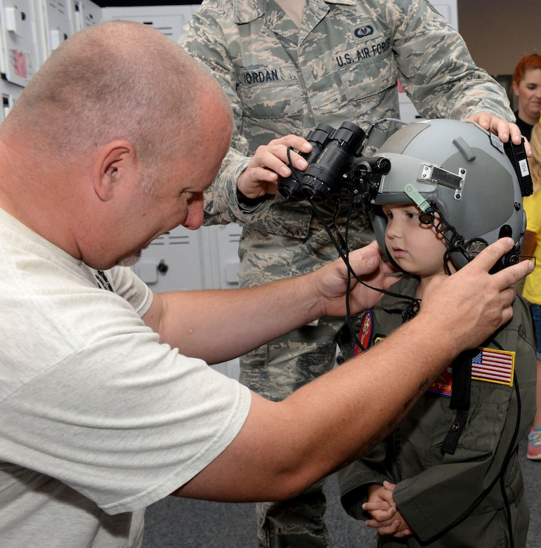 ALTUS AIR FORCE BASE, Okla. – Cody Dugger helps his son, Jaxon, put on a flight helmet equipped with nightvision goggles at the 97th Operations Support Squadron, June 26, 2015. Jaxon was diagnosed with Ewing's sarcoma when he was two years old. (U.S. Air Force photo by Airman 1st Class Kirby Turbak/Released)