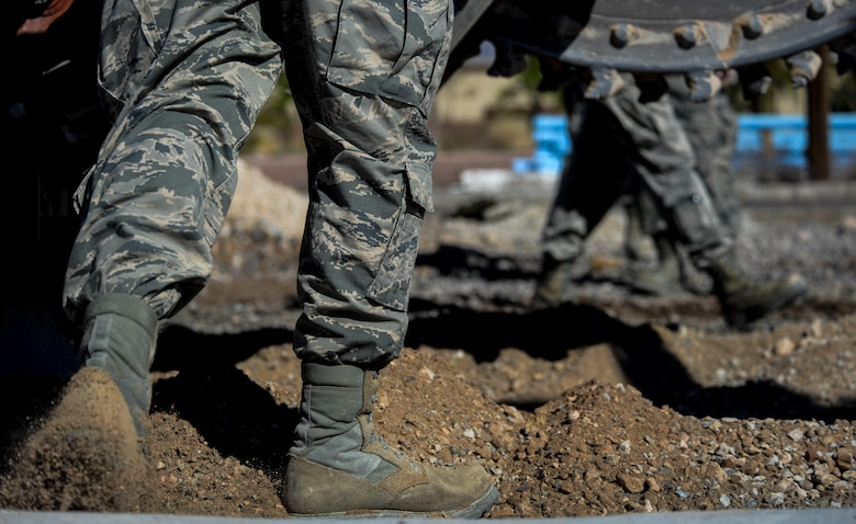 An Airman, assigned to the 555th Red Horse Squadron, kicks the dirt back from the freshly dug trench at Nellis Air Force Base, Nev., April 2, 2016. The contributions that the 555th RHS is able to provide can in part be attributed to how closely the squadron is able to coexist with its sister flight, the 820th RHS. (U.S. Air Force photo by Airman 1st Class Kevin Tanenbaum)