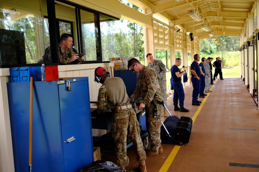 Staff Sgt. Jordan Locke, 647th Security Forces Squadron Combat Arms instructor, provides instructions during the Excellence in Competition pistol event, held 29-31 March, at the 647th SFS Combat Arms Firing Range on Schofield Barracks. (U.S. Air Force photo by Staff Sgt. Christopher Stoltz/Released)