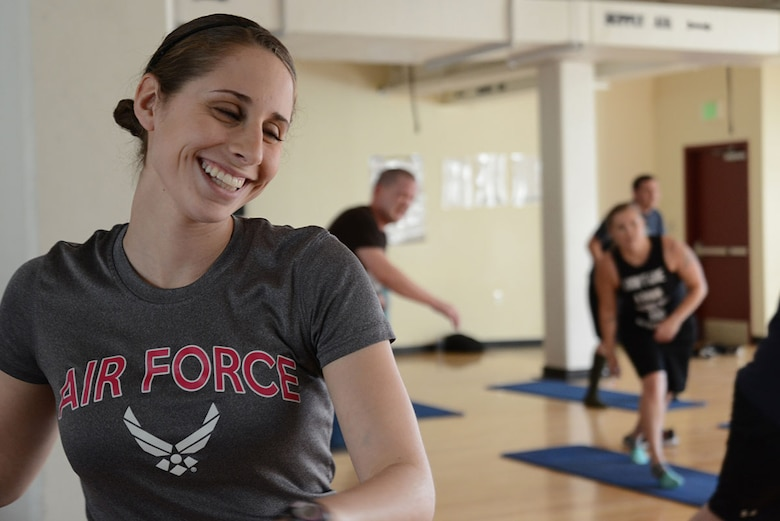 Airman 1st Class Nicole Rent, 703d Aircraft Maintenance Squadron aerospace maintenance apprentice, laughs while working out in a PiYo class at the Elmendorf Fitness Center, Joint Base Elmendorf-Richardson, Alaska, March 22, 2016. The Women's Health Clinic recommends pregnant women work out throughout pregnancy, preferably with others for support. (U.S. Air Force photo by Airman 1st Class Christopher R. Morales)