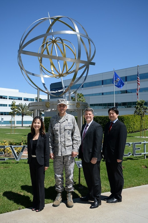 Members of the Space and Missile System Center's Directorate of Financial Management and Comptroller, from left to right, Jenny Tang, SMC/FM deputy director, Col. James Bell, SMC/FM director, John Karns, SMC/FM Cost Estimating Branch chief, and Chinson Yew, SMC Financial Management Cost Division acting chief, stand in front of the Armillary or Space Motif landmark on the grounds of the Schriever Space Complex at Los Angeles Air Force Base in El Segundo, Calif. The Cost Centralization Team recently earned a Special Acts and Services Award as part of the Fiscal Year 2015 Air Force Financial Management and Comptroller awards program for saving over $76 million in budgeted Air Force funding through their cost centralization initiatives. (U.S. Air Force photo/Van De Ha)