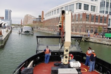 The crew on board the Reynolds, U.S. Army Corps of Engineers' steel debris vessel, approaches the Waterwheel Powered Trash Interceptor, also known as Mr. Trash Wheel, located in the Baltimore Inner Harbor on April 4, 2016. Col. Edward Chamberlayne, Commander, Baltimore District, visited with the team behind Mr. Trash Wheel to discuss similarities in their respective missions toward a cleaner Baltimore Harbor.