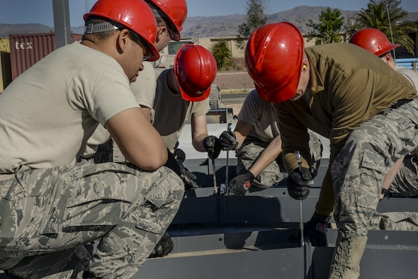 Airmen, assigned to the 555th Red Horse Squadron, tighten bolts on structures that will become the roof of the new firehouse at Nellis Air Force Base, Nev., April 2, 2016. What make the 555th an invaluable asset to Nellis AFB are the relationships it shares with other squadrons on base, including the 820th RHS. (U.S. Air Force photo by Airman 1st Class Kevin Tanenbaum)