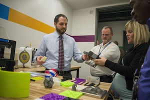 Jonathan Hopkins, a mechanical engineer and Additive Manufacturing (AM) Tiger Team member, shows fellow employees at Naval Surface Warfare Center, Carderock Division objects created through AM during a tour of the new Manufacturing, Knowledge and Education (MAKE) Lab, which officially opened in Building 60 in West Bethesda, Md., March 24, 2016. The MAKE Lab will open training and production in AM, also known as 3-D printing, to all of Carderock's employees