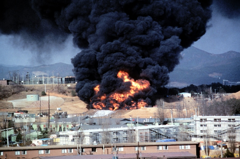 Smoke and flames billow from a 40,000-gallon fuel tank after an explosion at Osan Air Base, Republic of Korea, April 5, 1986. Thirty years after the explosion, the 51st Logistics Readiness Squadron performed a ceremony to honor the 16 individuals who lost their lives. (Courtesy Photo)
