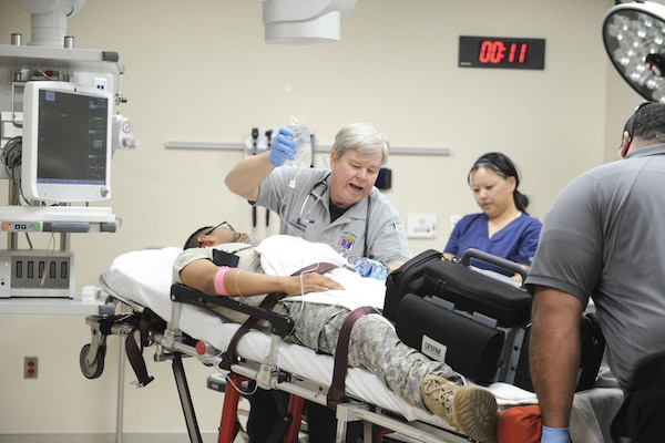 "Paramedics and emergency department (ED) staff rush in a volunteer patient for a simulated trauma case during the Carl R. Darnall Army Medical Center ""Day in the Life"" event preparing the staff for the new hospital facility on Feb. 6. The ED moved into the new facility April 3."