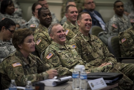 Brig. Gen. Phillip Jolly and Sgt. Maj. Mike Schultz, both with the Army Reserve Engagement Cell (AREC), U.S. Army Europe, Germany, share a laugh as a fellow AREC member from U.S. Army North takes the stage to brief the 200th Military Police Command headquarters leadership during a four-day workshop and Yearly Training Brief conference held in Columbus, Ohio, on April 2. AREC members from various Army Service Component Commands attended this YTB in order to grow partnerships between the 200th MP Cmd. and Army component commands across the globe. (U.S. Army photo by Master Sgt. Michel Sauret)