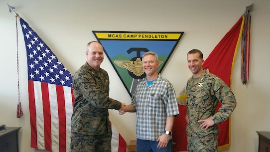Marine Corps Air Station Camp Pendleton, Calif. -- Col. Ian R. Clark, left, Commanding Officer, and Lt. Col. David Fairleigh, right, Executive Officer of MCAS Camp Pendleton, congratulate Mr. Robert C. McCoy, center, Assistant Air Traffic Control Facility Officer in the ATC Facility, MCAS Camp Pendleton, on being awarded the 2015 Marine Corps Installation Command Senior General Schedule Category Employee of the Year, March 11, 2016.