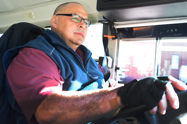 Glenn H. Bulaon, a shuttle bus driver for Skookum Contract Services, prepares to board passengers onto a shuttle bus at Fort Meade on March 21. Bulaon has been driving the shuttle bus for the Defense Information School here since 2010, and he says he enjoys driving for the students because it bring him a sense of purpose.