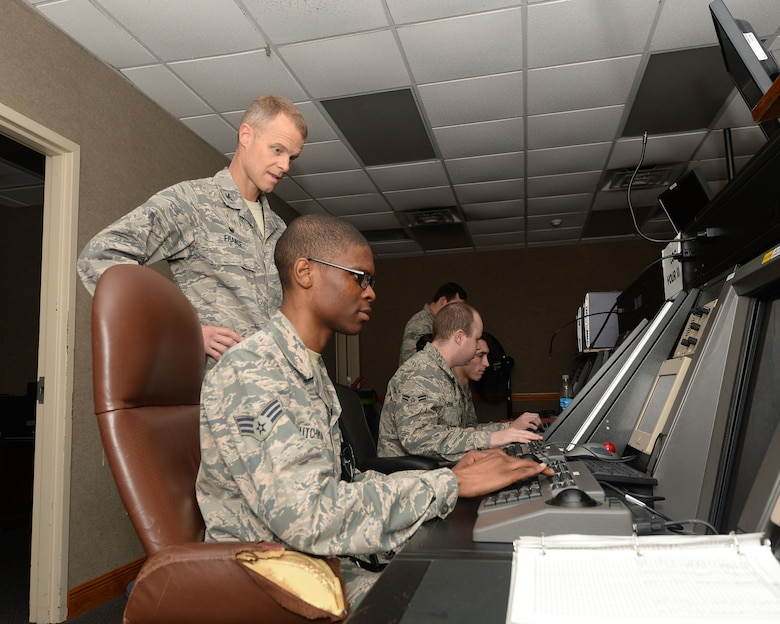During the Airman's Shadow Program, Col. Derek C. France, 325th Fighter Wing commander, observes Senior Airman Jonathan Hutchinson, 325th Operations Support Squadron air traffic controller, while he runs a simulation that trains air traffic controller trainees on how to coordinate jets in the air March 29, 2016. The Airman's Shadow program is a 325th FW commander program designed to recognize members of Team Tyndall. The program provides an opportunity for the commander to meet with the Airmen and get a first-hand look at what Tyndall Airmen are doing. (U.S. Air Force photo by Airman 1st Class Cody R. Miller/Released)
