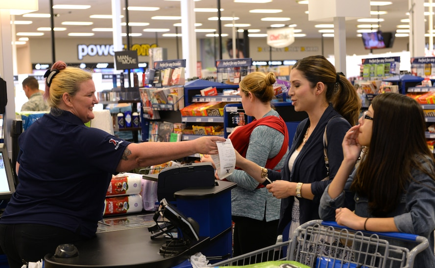 An Army Air Force Exchange Services Exchange cashier hands a receipt to a customer at Barksdale Air Force Base, La., March 31, 2016. The Exchange hosted a grand reopening to unveil recent improvements which included new and improved departments, product lines and customer services. (U.S. Air Force photo/Airman 1st Class Curt Beach)