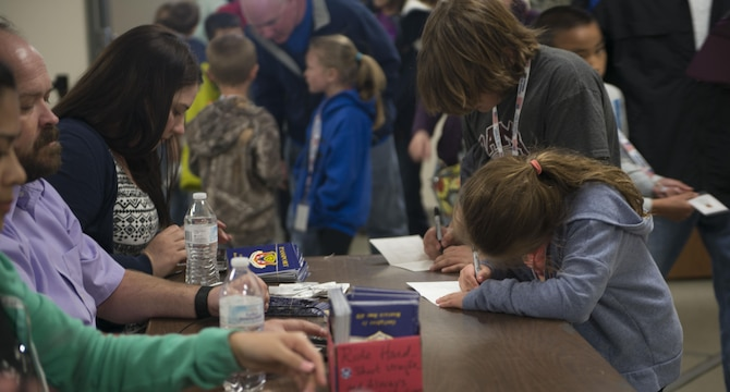 A child writes her name on her Gunfighter Jr. passport April 4, 2016, at Mountain Home Air Force Base, Idaho. Children of deployed service members had the opportunity to walk through a mock deployment line and experience the process of a deployment. (U.S. Air Force photo by Senior Airman Malissa Lott/RELEASED)