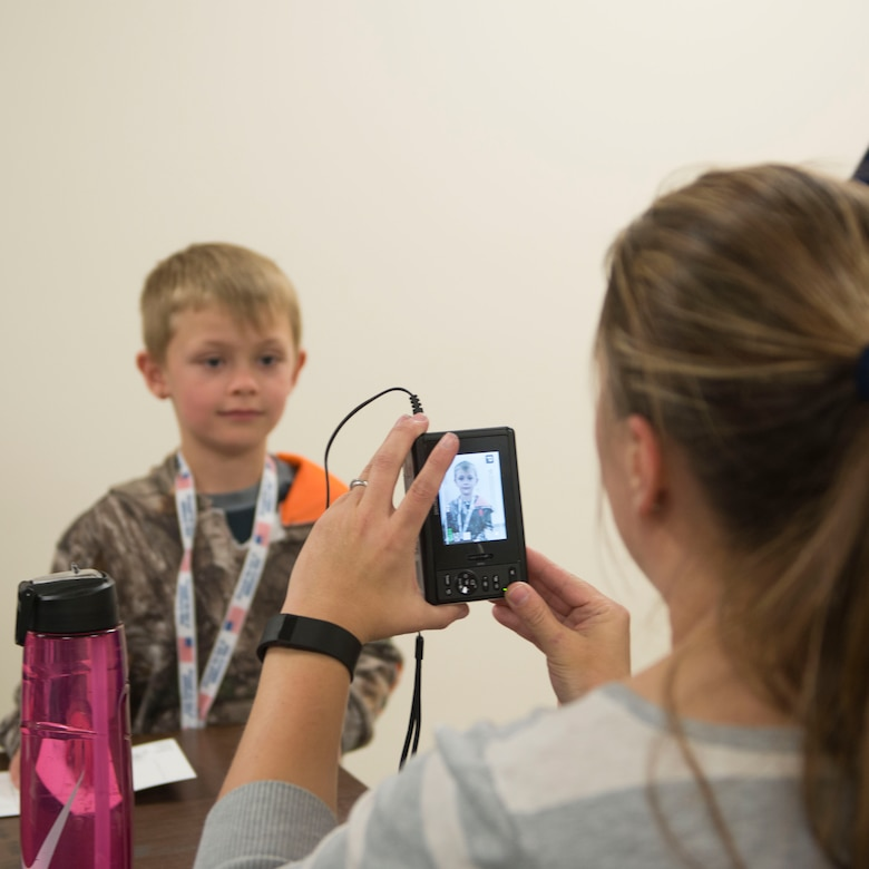 A child has his picture taken for his Gunfighter Jr. passport April 4, 2016, at Mountain Home Air Force Base, Idaho. Gunfighter Jr. allowed children of service members to experience what their parent does to prepare for a deployment. (U.S. Air Force photo by Senior Airman Malissa Lott/RELEASED)