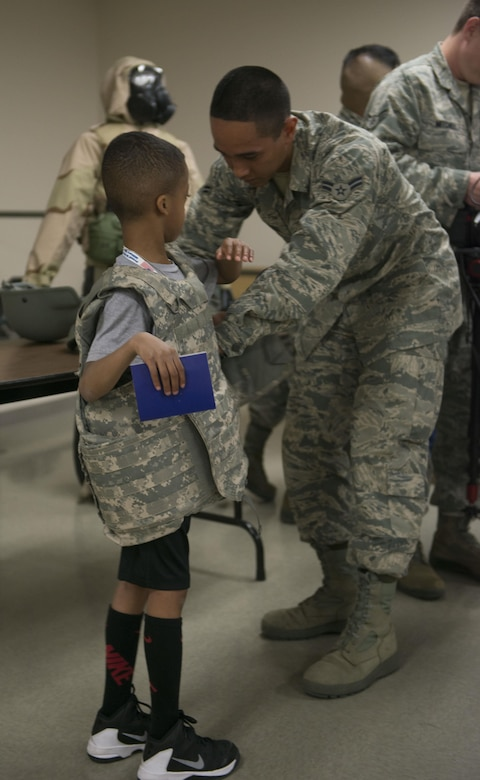 """A child tries on Kevlar as part of the Gunfighter Jr. event April 4, 2016, at Mountain Home Air Force Base, Idaho. Gunfighter Jr. provided the children with their own Gunfighter Jr. passports and their own """"readiness bags"""" full of prizes. (U.S. Air Force photo by Senior Airman Malissa Lott/RELEASED)"""