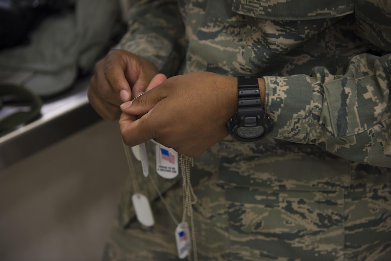 An Airman detangles mock dog tags for children attending the Gunfighter Jr. event April 4, 2016, at Mountain Home Air Force Base, Idaho. These dog tags were handed out to children participating in the event. (U.S. Air Force photo by Airman Alaysia Berry/Released)