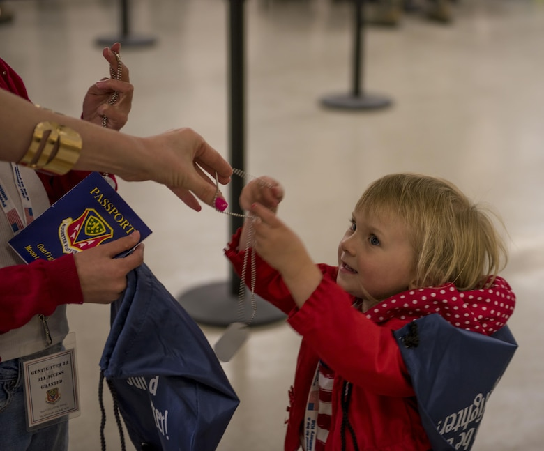 A child recieves dog tags, a passport, and a readiness bag filled with other items April 4, 2016, at Mountain Home Air Force Base, Idaho. The goodies were given to children who walked through the mock deployment line. (U.S. Air Force photo by Airman Alaysia Berry/Released)