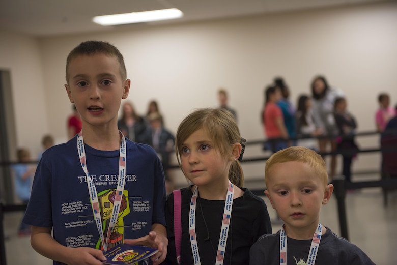 Three children stand in a mock deployment line at Gunfighter Jr. April 4, 2016 at Mountain Home Air Force Base, Idaho. During Gunfighter Jr. kids learn firsthand what it's like when a parent deploys. (U.S. Air Force photo by Airman Alaysia Berry/Released)