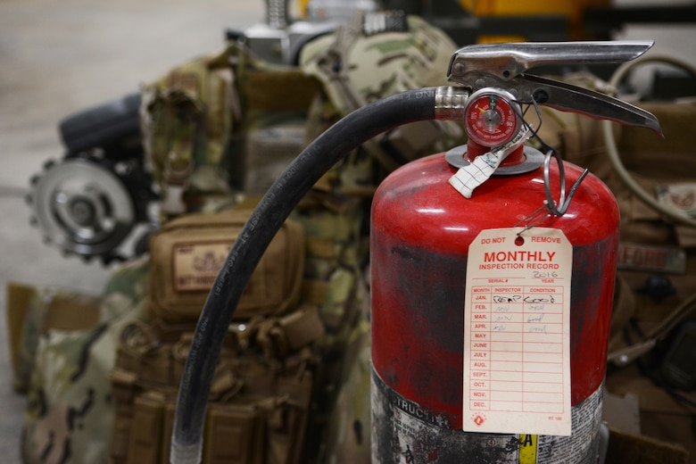 A fire extinguisher sits on the ground of an Explosive Ordnance Disposal storage space at the 115th Fighter Wing in Madison, Wis., April 6, 2016. The fire extinguisher was used by an EOD Airman to put out a car fire after coming across the one-car accident on the highway. (U.S. Air National Guard photo by Staff Sgt. Andrea F. Rhode)
