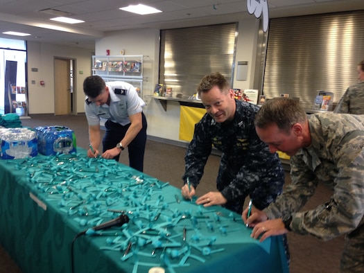 Sexual Assault Awareness Month is recognized every April to raise awareness about sexual violence and help educate the community on how to reduce the risk of it occurring. Col. Christopher Finerty, ANGRC Acting Commander, CAPT Scott Fuller, NAFW Commander and Col. Bradley Hoagland 11th Wing Commander signed teal ribbons at the Community Commons, on April 4, in a pledge of support to help end sexual violence by addressing inappropriate behavior and treating others with dignity and respect. (Photo by Andrea Verdino)