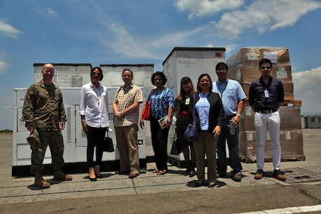 """Members from the Philippine Department of Health, USAID and U.S. Navy pose for a photograph during a turnover of humanitarian assistance equipment during exercise Balikatan in Subic, Philippines April 6, 2016. The exercise provided an opportunity to deliver the equipment on U.S. Naval Ships to the Philippines. Balikatan, which means """"shoulder to shoulder"""" in Filipino, is an annual bilateral training exercise focused on improving the ability of Philippine and U.S. military forces to work together during planning, contingency and humanitarian assistance and disaster relief operations."""