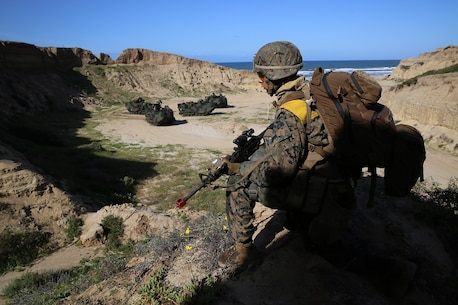 A Marine with Company B, 1st Battalion, 4th Marines looks for enemy movement from atop a hill as Assault Amphibious Vehicles stage for the next phase of Co. B's Marine Corps Combat Readiness Evaluation aboard Marine Corps Base Camp Pendleton, Calif., March 29, 2016. The week-long assessment tests Co. B's competency before a deployment later in the year. (U.S. Marine Corps photo by Lance Cpl. Timothy Valero/ Released)