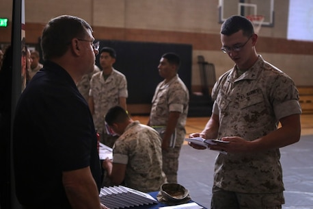 Daniel R. Bennett, a military service coordinator, speaks to a Marine with 1st Marine Regiment, 1st Marine Division, during a career fair held aboard Marine Corps Base Camp Pendleton, Calif., March 6, 2016. Representatives with law enforcement groups, explosive ordnance disposal units, Marine Special Operation Command, and higher education organizations participated in the fair to expose the Marines to post-service opportunities.
