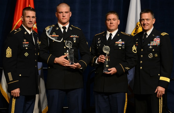 Sgt. Maj. of the Army Daniel A. Dailey, far left, and Army Vice Chief of Staff Gen. Daniel B. Allyn, far right, present the Soldier of the Year award to Spc. Jared R. Tansley, assigned to U.S. Army Europe, and the Noncommissioned Officer of the Year award to Staff Sgt. Andrew Fink, assigned to U.S. Army Reserve Command, during the 2015 Best Warrior Competition Awards Ceremony at the annual meeting of the Association of the United States Army in Washington, Oct. 12, 2015.