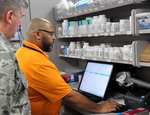 Dwain Hedgepeth, 22nd Medical Support Squadron supply custodian, demonstrates the base pharmacy procedures to Col. Albert Miller, 22nd Air Refueling Wing commander, March 31, at McConnell Air Force Base, Kan. Miller visited the clinic to better understand how patients are processed through the line and how electronic prescriptions are filled and tracked in the system. (U.S. Air Force photo/Senior Airman David Bernal Del Agua)