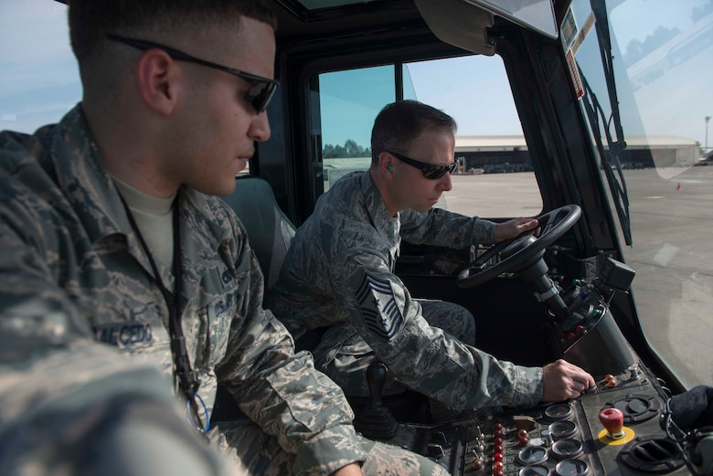 U.S. Air Force Chief Master Sgt. Mark Redden, 521st Air Mobility Operations Wing command chief, starts a U-30 aircraft tow vehicle while U.S. Air Force Staff Sgt. Michael Salcedo, 728th Air Mobility Squadron crew chief, monitors him, April 5, 2016, at Incirlik Air Base, Turkey. During his visit, Redden toured the 728th AMS facilities and interacted with Airmen throughout the day. (U.S. Air Force photo by Senior Airman John Nieves Camacho/Released)
