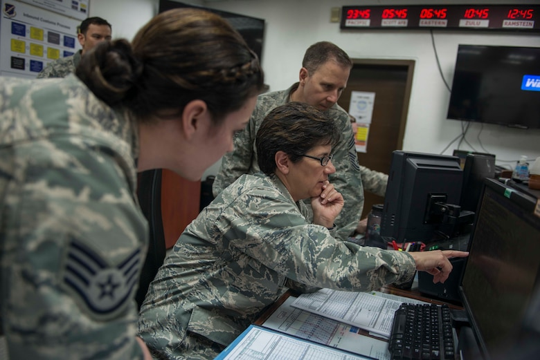 U.S. Air Force Col. Nancy Bozzer, 521st Air Mobility Operations Wing commander, reviews aerial port operations with U.S. Air Force Staff Sgt. Brittany Ogletree, 728th Air Mobility Squadron air terminal operations information controller, and U.S. Air Force Chief Master Sgt. Mark Redden, 521st AMOW command chief, April 4, 2016, at Incirlik Air Base, Turkey. Bozzer presented Ogletree with a commander's coin for her recent duty performance. (U.S. Air Force photo by Senior Airman John Nieves Camacho)