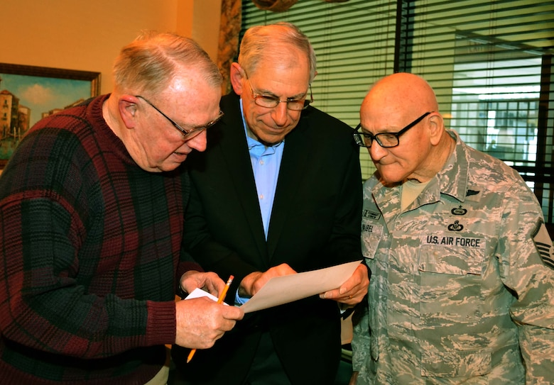 From left to right, retired Col. Lou Meier, former 111th Fighter Wing commander; retired Lt. Col. Gary Yudell, former 111th FW O-2 Skymaster and A-37 Dragonfly pilot; and retired Master Sgt. Jim Waibel, currently a historian for the 111th Attack Wing at Horsham Air Guard Station, Pa. view and old photograph during the Wing's 74th annual 111th Attack Wing Retirees Dinner in Philadelphia, April 4, 2016. The yearly dinner hosts retirees, current members and associated 111th Attack Wing staff for an evening of socialization between Pa. Air National Guard members. (U.S. Air Force photo by Tech. Sgt. Andria Allmond)