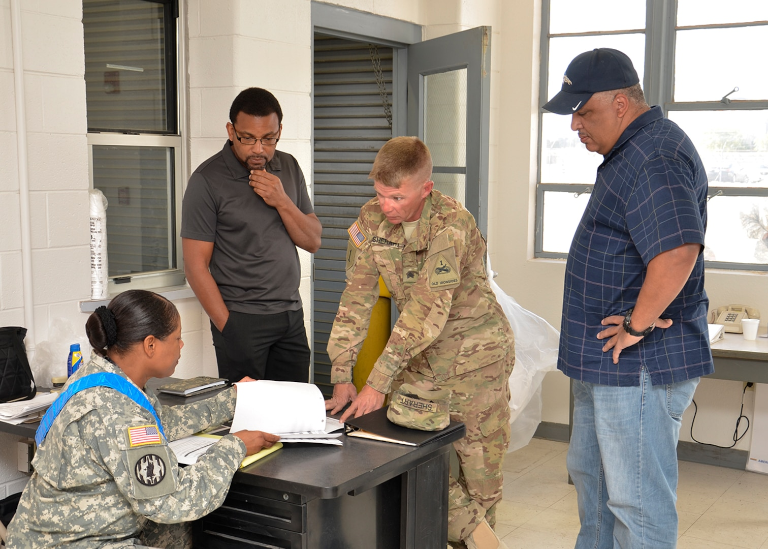 """A soldier from the Army control cell (seated) disscuses paper work issues with another soldier while Jason Middleton, chief of the DLA Distribution expeditionary team (second from left) and DLA Disposition Services West Director Christopher """"Buck"""" Buchanan (far right) listen in for the outcome."""