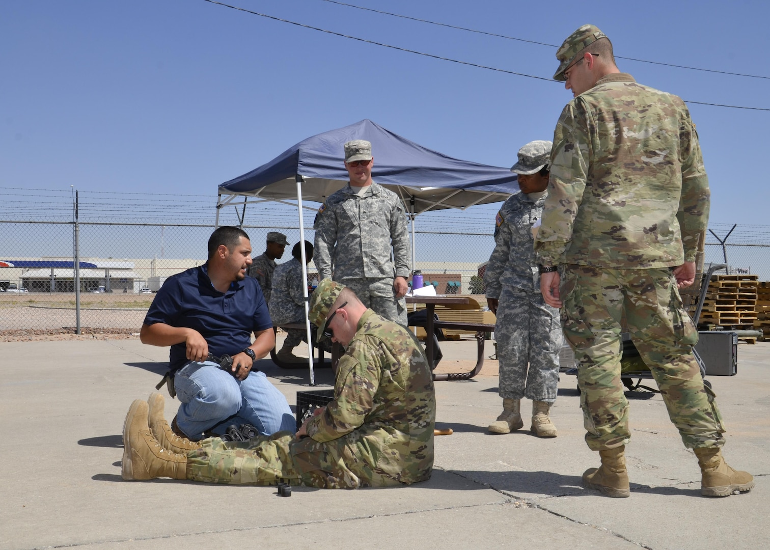 Ray Menendez (blue shirt) a material examiner at DLA Disposition Services Fort Bliss, Texas. Helps a solider with items he is turning in for disposal while soldiers from other units ask Menendez questions concerning the property they are turning in.