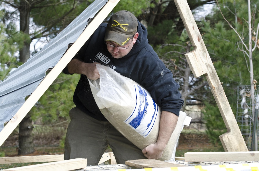 Joe Villines, an Army Sgt. with the U.S. Army Reserve pours a bag of organic chicken feed into a newly constructed chicken pen on his farm in Cummings, Iowa, March 18, 2016. Villines manages to find the balance between his military obligations, his civilian career with the Department of Veterans Affairs, fatherhood, and a growing passion in rural farming. Joe is increasing his knowledge on traditional farming and becoming a man of the soil, and in the process giving back to his local community.(U.S. Army Reserve photo by  Brian Godette, USARC Public Affairs)