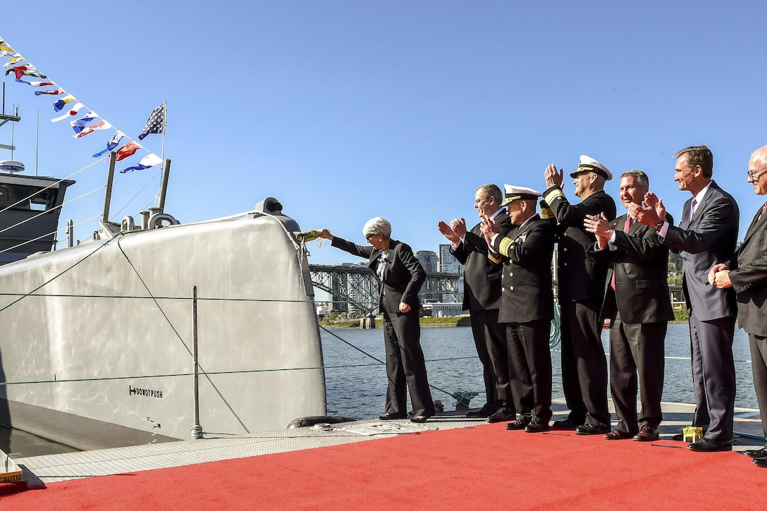 Deputy Defense Secretary Bob Work, second from left, celebrates during a Defense Advanced Research Projects Agency christening ceremony for a technology demonstration vessel in Portland, Ore., April 7, 2016. DARPA's anti-submarine warfare continuous trail unmanned vessel program designed, developed and built the vessel. DoD photo by Army Sgt. 1st Class Clydell Kinchen
