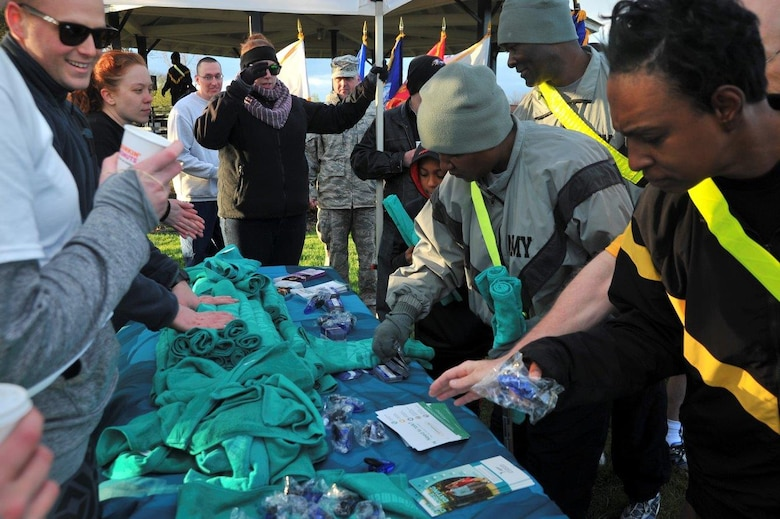 70th Intelligence, Surveillance and Reconnaissance Wing Sexual Assault Prevention and Response office, Volunteer Victim Advocates, and Sexual Harassment/Assault Response and Prevention office member pass out informational gifts after the 2016 Sexual Assault, Awareness and Prevention Month garrison run April 8, 2016 at Fort George G. Meade, Md. There were over 1,900 joint service members participating in the SAAPM event. (U.S. Air Force photo/Staff Sgt. Alexandre Montes)