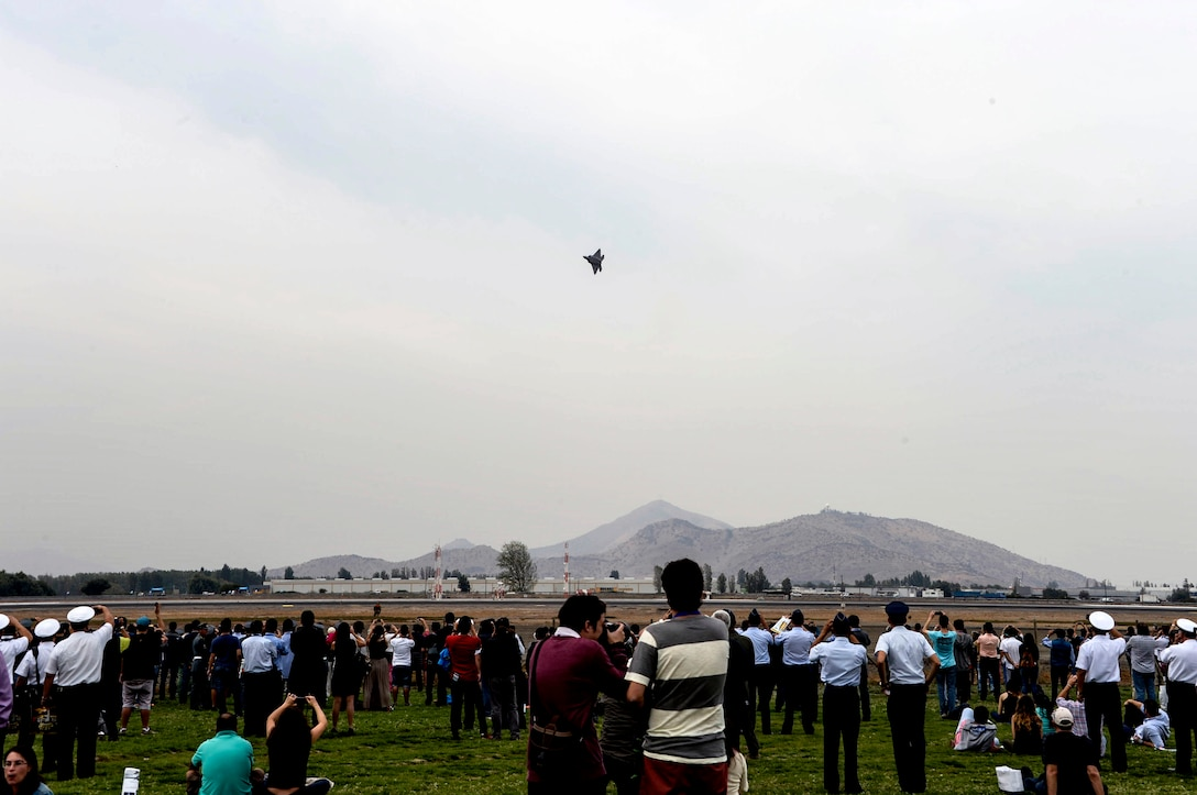 Crowds gather to watch an F-22 Raptor, from the F-22 Raptor Demonstration Team at Langley AFB, Va., performs its aerial acrobatics routine at the 2016 International Air and Space Fair (FIDAE) in Santiago, Chile, April 1, 2016. During FIDAE, U.S. Airmen participated in in several subject matter expert exchanges with their Chilean counterparts and also hosted static displays and aerial demonstrations to support the air show.  (U.S. Air Force photo by Tech. Sgt. Heather Redman/Released)