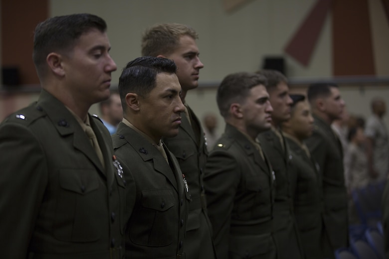 Basic Communications Officer Course 1-16 students stand at the position of attention during the playing of the national anthem during the course's graduation ceremony at the base theater April 1, 2016. (Official Marine Corps Photo by Cpl. Julio McGraw/Released)