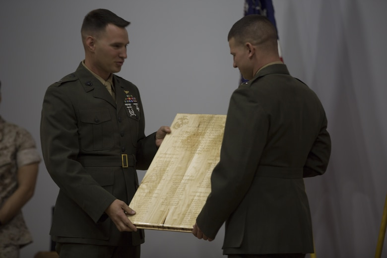 Captain Dimitri Stepanoff, executive officer, Communication Training Battalion, accepts a gift presented to him from students of the Basic Communications Officer Course 1-16 during the course's graduation ceremony at the base theater April 1, 2016. (Official Marine Corps Photo by Cpl. Julio McGraw/Released)