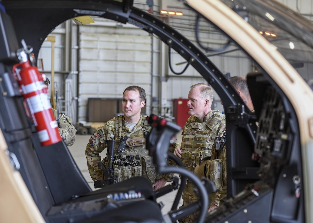 Chief Master Sgt. of the Air Force James A. Cody and Tech. Sgt. Daniel Bogan, a rotary wing gun air advisor, listen as a train, advise and assist pilot discusses Afghan air force progress with the MD-530 light attack helicopter at Hamid Karzai International Airport, Afghanistan, April 6, 2016. During his trip, Cody engaged with Airmen deployed to Afghanistan in support of the NATO Resolute Support mission and Operation Freedom's Sentinel through a series of question-and-answer all calls, small group discussions and personal site visits. (U.S. Air Force photo/Tech. Sgt. Nicholas Rau)